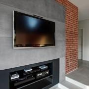 telewizor wiszący na betonowej ścianie